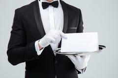 Butler en smoking y guantes que sostienen la tarjeta en blanco en la bandeja Imagenes de archivo