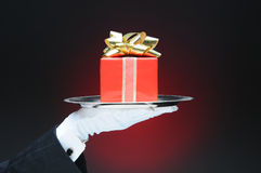 Butler With Gift on Tray. A butler wearing a tuxedo and white glove holding a tray with a wrapped present. Hand and arm only over a light to dark red background royalty free stock image