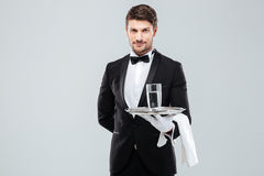 Butler in gloves holding glass of water on silver tray. Confident young butler in tuxedo and gloves holding glass of water on silver tray royalty free stock photo