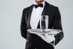 Butler in gloves holding silver tray with glass of water. Closeup of butler in tuxedo and gloves holding silver tray with glass of water royalty free stock photography