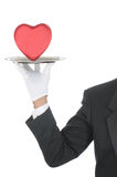Butler with Heart on Tray. Butler wearing tuxedo and formal gloves holding a heart shaped box on a silver tray. Shoulder hand and arm only isolated on white royalty free stock photography