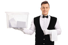 Butler holding a ballot box filled with votes stock photography
