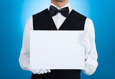 Butler holding blank billboard Royalty Free Stock Photo