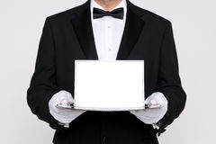 Butler holding a blank card upon a silver tray. Butler holding a blank card upon a silver service tray, add your own message royalty free stock photo