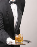 Butler holding Cocktail on tray. Waiter in tuxedo Presenting Cocktail on silver tray vertical format torso only royalty free stock images