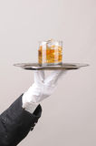 Butler holding Cocktail on tray. Waiter in tuxedo Presenting Cocktail on silver tray closeup vertical format hand and arm only stock image