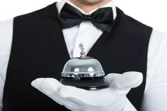 Butler holding service bell. Midsection of young butler holding service bell over white background stock photo