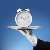 Butler holding silver tray with a alarm clock Royalty Free Stock Images