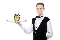 Butler holding a silver tray with a clock. A butler holding a silver tray with a alarm clock on it stock photo
