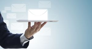 Business information update via email notification. Butler holding a tablet serving most updated business information via email notification to customers for Stock Photo