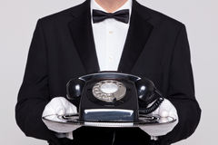 Butler holding a telephone on silver tray Royalty Free Stock Image
