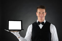 Butler Holding Tray With Digital Tablet. Young Butler Holding Tray With Blank Display Digital Tablet stock image