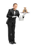 Butler holding a tray with a money bag on it stock photo