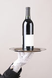 Butler holding wine bottle on tray royalty free stock photo