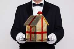 Butler holding your new home. Butler holding a gift wrapped model building on a silver tray, good concept image for Moving, New Home, Relocation or House buying Stock Photo