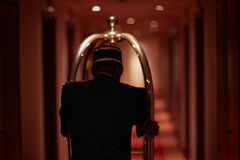 Butler in hotel. Rear view of servant moving along hotel aisle with baggage cart Royalty Free Stock Image