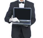 Butler with Laptop Computer. Butler in tuxedo holding a laptop computer facing camera pressing button- torso only Royalty Free Stock Images