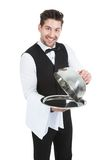 Butler lifting cloche from serving tray Stock Photography