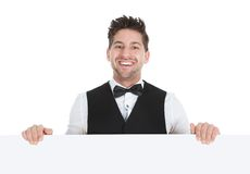 Butler looking at blank billboard. Young butler looking at blank billboard isolated over white background royalty free stock photos