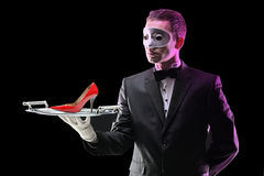 Butler with a mask holding a tray. With high heel on it stock photo
