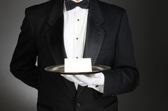 Butler With Note on Tray. A butler wearing a tuxedo holding a note card on a silver tray in front of his torso. Man is unrecognizable over a light to dark gray Stock Photo