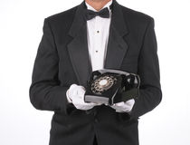 Butler with phone. Butler with old rotary telephone in his hands. Torso shot isolated over white stock photo