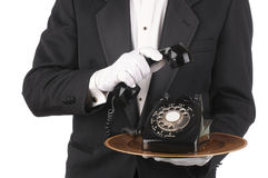 Butler with Phone on Tray. Butler Holding an Old Rotary Telephone on a tray with the receiver in his other hand isolated on white torso only stock photo