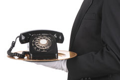 Butler with Phone on Tray. Butler Holding an Old Rotary Telephone on a tray isolated on white side view of person torso only royalty free stock photography
