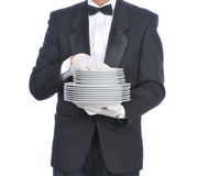Butler with Plates. Butler in tuxedo carrying a stack of plates - torso only stock photos