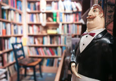 Butler puppet. Butler puppet with bow, mustache and jacket inviting to enter inside an old book store Stock Photos