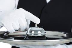 Butler que sostiene la campana del servicio Foto de archivo libre de regalías