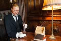 Butler serving a drink. Portrait of a wax butler figure wearing black suit and white gloves, serving a drink. Warwick Castle, Warwickshire, England royalty free stock images