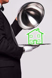 Butler serving a new home. Butler lifting the cloche from a silver serving tray to reveal a house illustration, good image for housing themes stock images