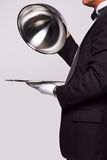 Butler and silver service. Butler lifting the cloche from a silver serving tray, insert your own object onto the tray Royalty Free Stock Photography