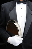 Butler with silver tray under his arm. Closeup of a butler with a silver tray under his arm. Man is wearing a tuxedo and white gloves showing torso only in stock photography