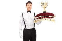 Butler tenant un trophée sur l'oreiller rouge Photo stock