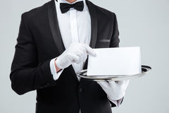 Butler in tuxedo and gloves holding blank card on tray. Closeup of butler in tuxedo and gloves holding blank card on tray stock images