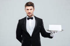 Butler in tuxedo and gloves holding tray with blank card. Attractive young butler in tuxedo and gloves holding tray with blank card stock photography
