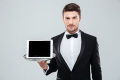 Butler in tuxedo holding blank screen tablet on tray. Portrait of attractive young butler in tuxedo with bowtie holding blank screen tablet on tray Stock Photography