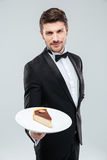 Butler in tuxedo holding piece of cake on plate stock image