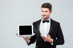 Butler in tuxedo holding and pointing at blank screen tablet. Confident young butler in tuxedo holding and pointing at blank screen tablet on tray stock images