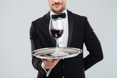 Butler in tuxedo holding silver tray with glass of wine stock image