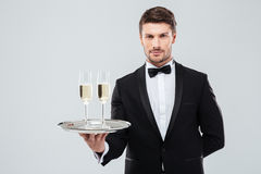 Butler in tuxedo holding tray with two glasses of champagne. Handsome young butler in tuxedo holding tray with two glasses of champagne royalty free stock photo