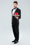 Butler in tuxedo standing and holding tray with gift box royalty free stock photography
