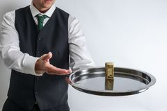 Butler / waiter holds a silver tray with a ten dollar bill. royalty free stock photos
