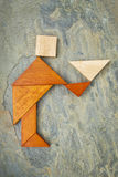Butler, waiter or servant figure. Abstract of a butler, waiter or servant figure built from seven tangram wooden pieces, a traditional Chinese puzzle game; slate royalty free stock photo