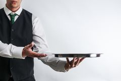 Butler / waiter in suit vest carrying an empty silver tray. Butler / waiter in white shirt and black suit vest carrying an empty silver tray. Copy space for royalty free stock image