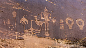 Butler Wash Wolfman Petroglyph panel. A petroglyph panel with a variety of humanoid and animal images portrayed on the cliffs of Butler Wash in the Comb Ridge stock photography
