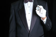Butler with Watch. Butler in Tuxedo Holding a Pocket Watch with the Face pointing towards camera stock photo
