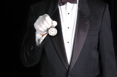 Butler with Watch. Butler in Tuxedo Holding a Pocket Watch with the Face pointing towards camera royalty free stock photography